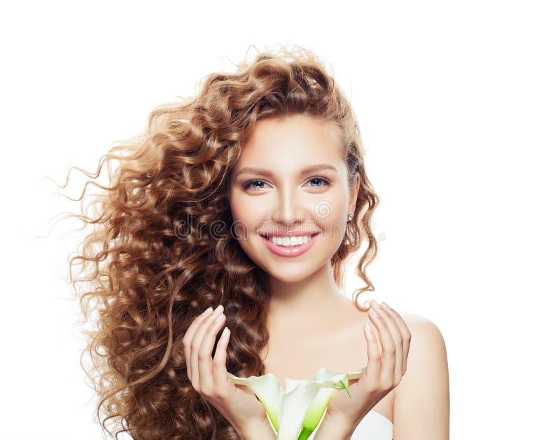 有在白色隔绝的长的卷发的微笑的妇女 与清楚的皮肤的美好的在手画象的模型和花 库存图片
