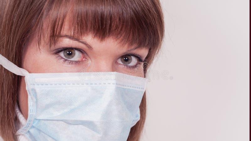 有在白色隔绝的面孔麝香的年轻女性医生 免版税库存图片