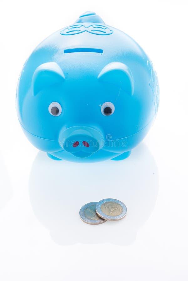 有在白色隔绝的金钱的蓝色存钱罐 免版税库存图片