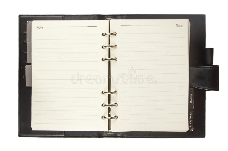 有在白色隔绝的黑盖子的空白的笔记本 库存照片