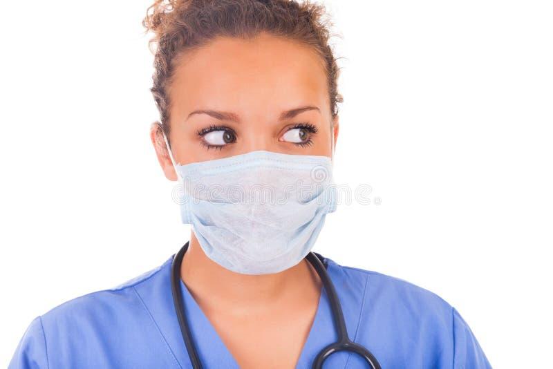 有在白色backgro和听诊器的年轻医生隔绝的面具 库存图片