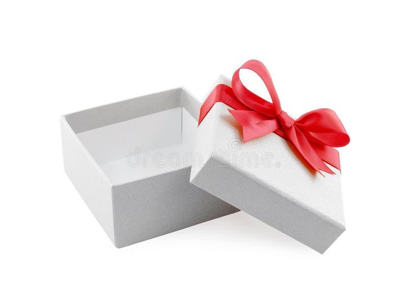 有在盒盖附近被包裹的红色丝带弓的开放和空的白色礼物盒隔绝在白色背景 免版税库存照片