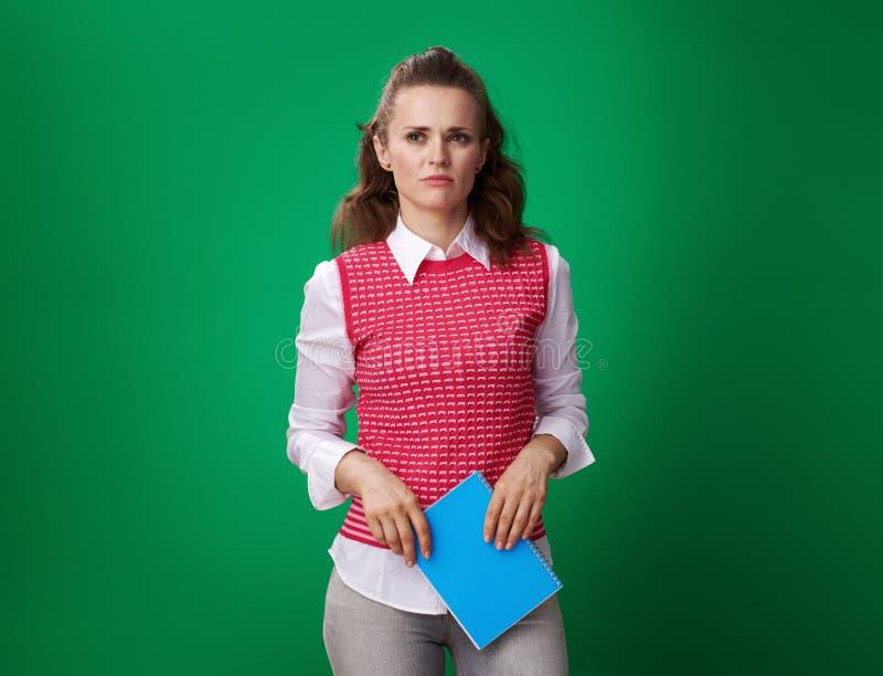 有在绿色隔绝的蓝色笔记本的不快乐的学生妇女 免版税库存照片