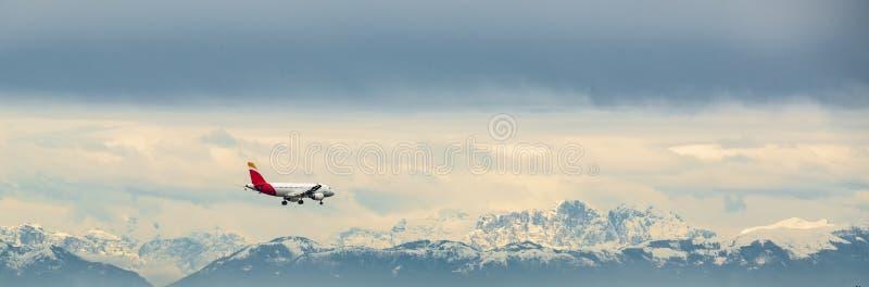 有在背景的雪盖的高山的客机 免版税库存图片