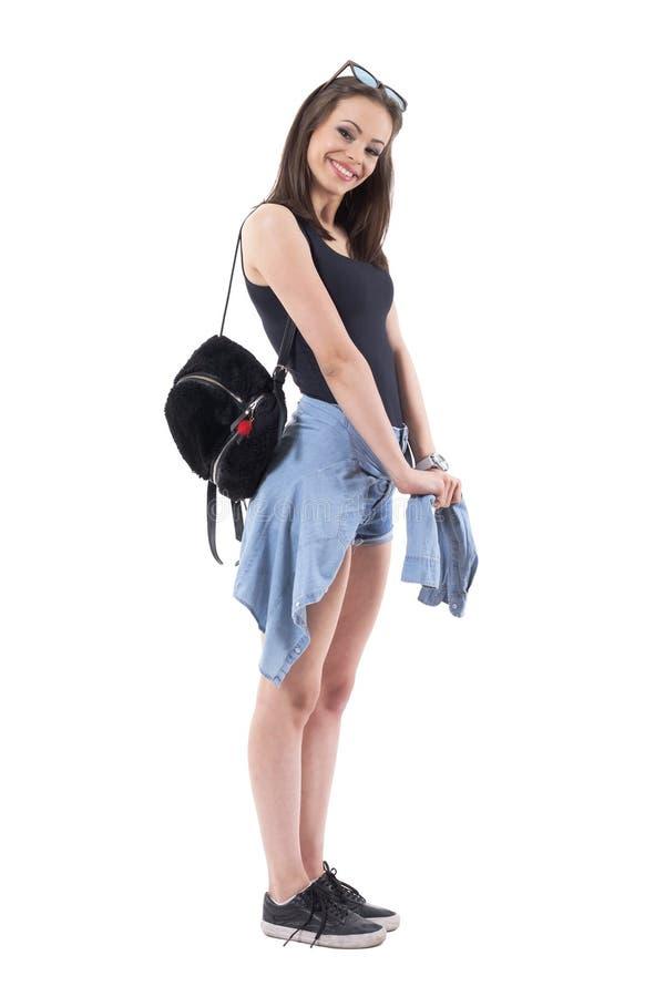 有在腰部附近被栓的豪华的袋子和牛仔布夹克的可爱的年轻时髦的妇女摆在和微笑 库存照片
