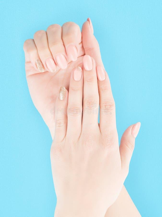 有在蓝色隔绝的红色指甲油的妇女手 免版税库存照片