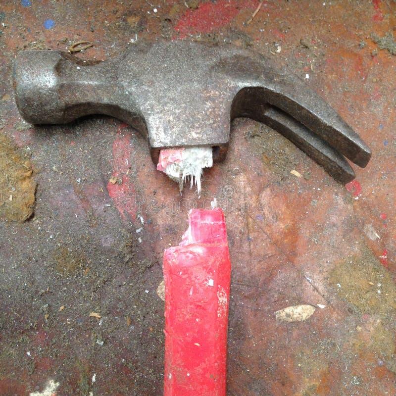 有在被弄脏脏的红色玻璃纤维把柄的老打破的锤子 库存图片