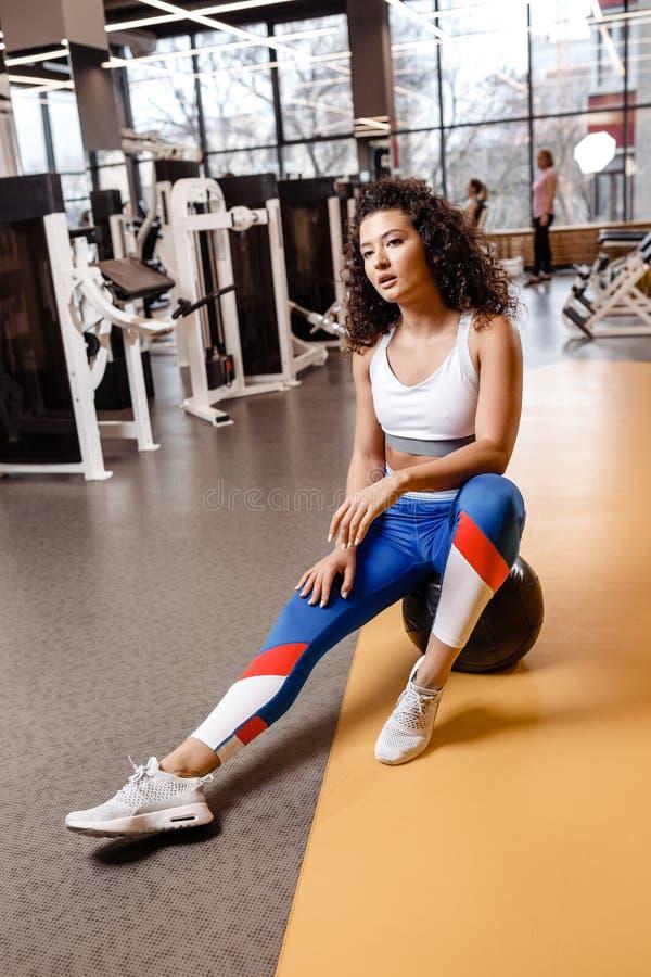 有在运动服穿戴的黑暗的卷发的亭亭玉立的女孩坐在现代健身房的健身球与大窗口 库存照片