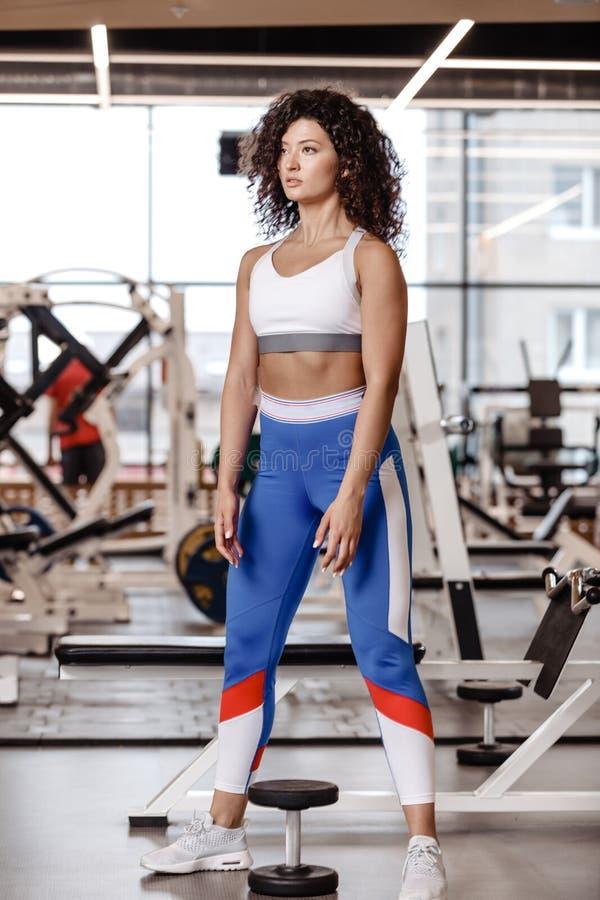 有在运动服is is穿戴的黑暗的卷发的亭亭玉立的女孩站立的下t在现代健身房的重的哑铃与 库存图片
