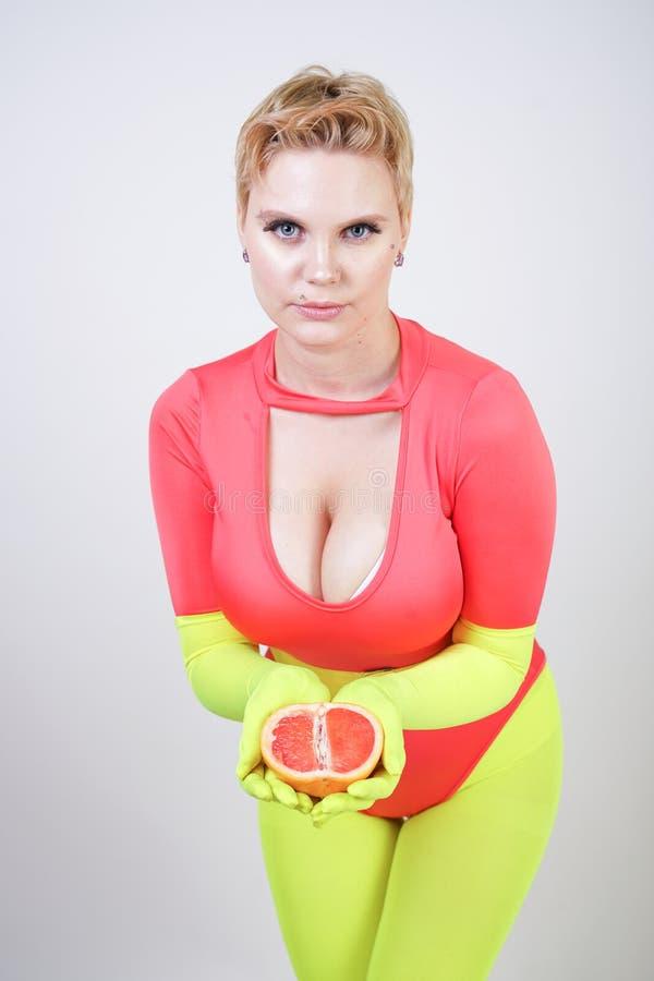 有在运动的红色氨纶紧身衣裤和明亮的贴身衬衣穿戴的短发的供选择的白种人女孩有绿色霓虹手套的 curvac 库存照片