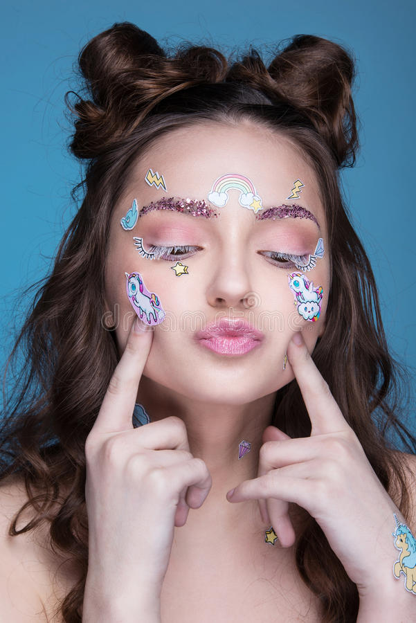 有在面孔胶合的滑稽的专业构成和emoji贴纸的美丽的时尚女孩 库存图片