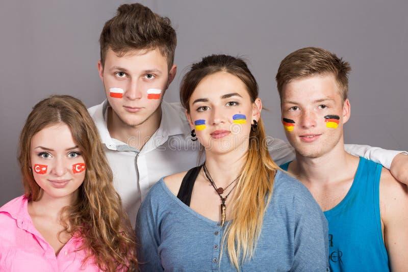 有在面孔画的旗子的四个少年 免版税库存照片