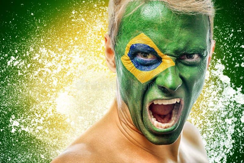 有在面孔绘的巴西旗子的人 免版税库存照片
