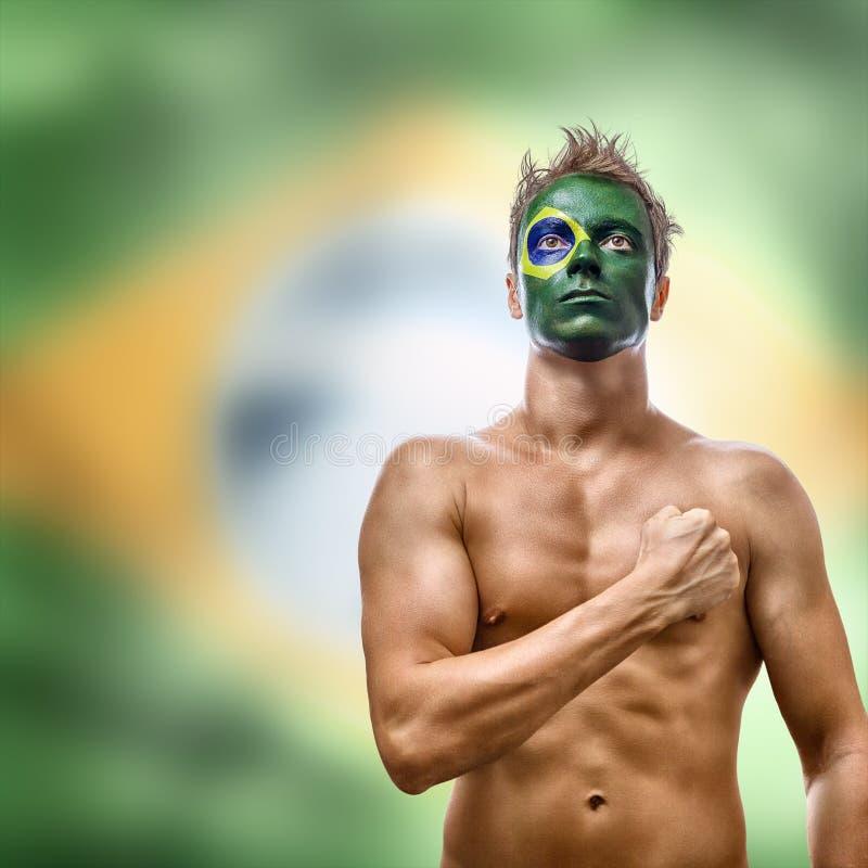有在面孔绘的巴西旗子的人 库存图片