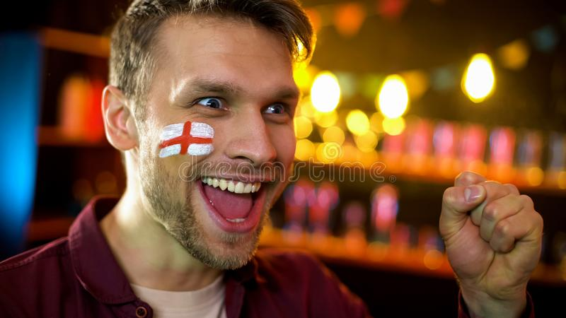 有在面颊欢呼绘的旗子的满意的英国足球队支持者 免版税库存图片