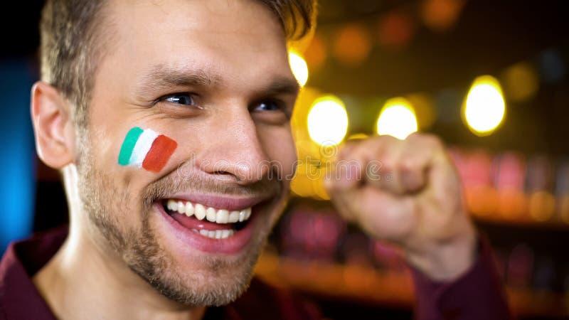 有在面颊绘的旗子的呼喊快乐的意大利的爱好者,队计分的目标 库存照片