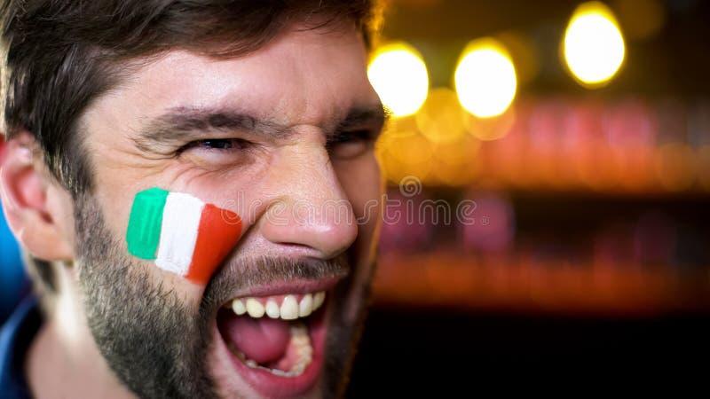 有在面颊绘的旗子的尖叫快乐的意大利的爱好者,队计分的目标,胜利 免版税库存照片