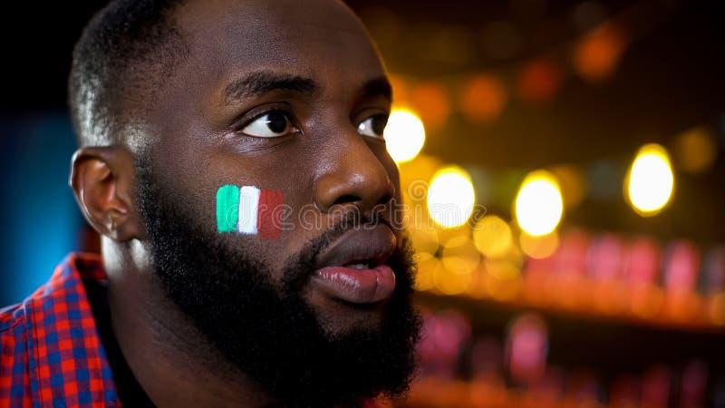 有在面颊观看的超大事件绘的意大利旗子的非裔美国人的人 库存照片