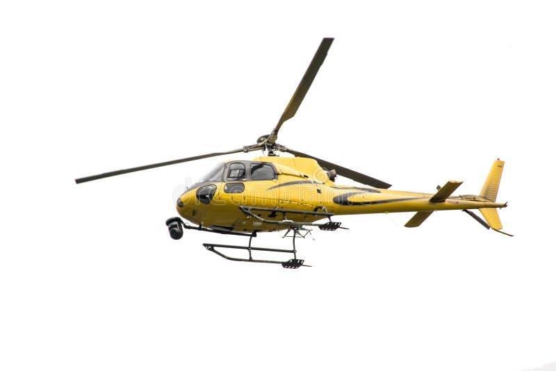 有在飞行中照相机的黄色直升机 免版税库存照片