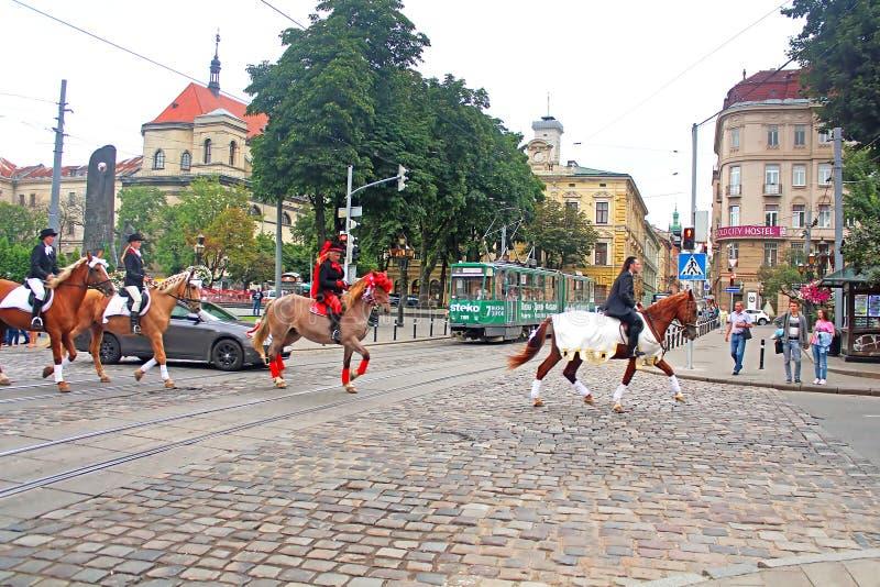 有在马背上车手的随从在街道上在历史市中心,利沃夫州 库存照片