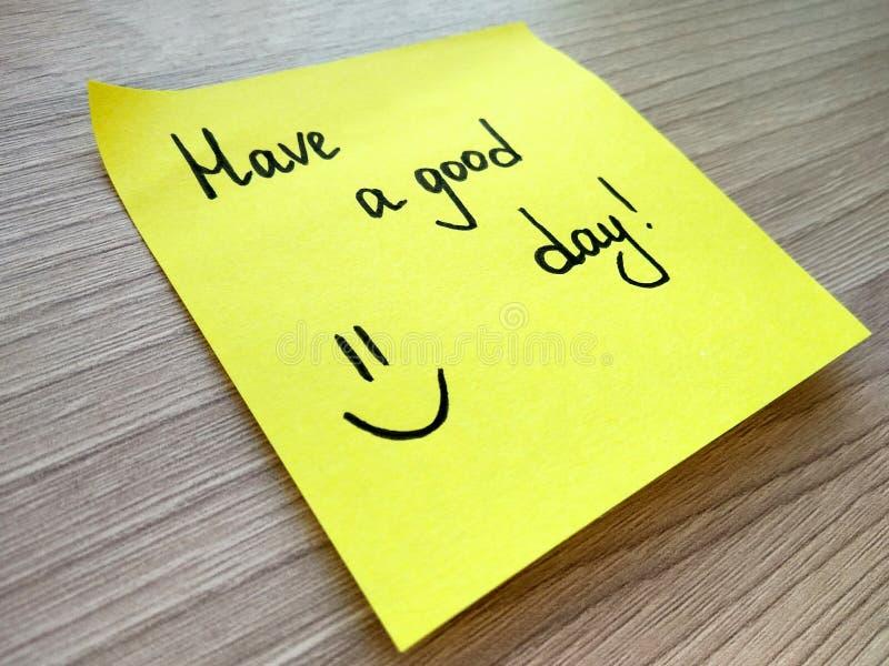 有在黄色稠粘的笔记的一则好日子手写的消息关于木背景 免版税库存照片