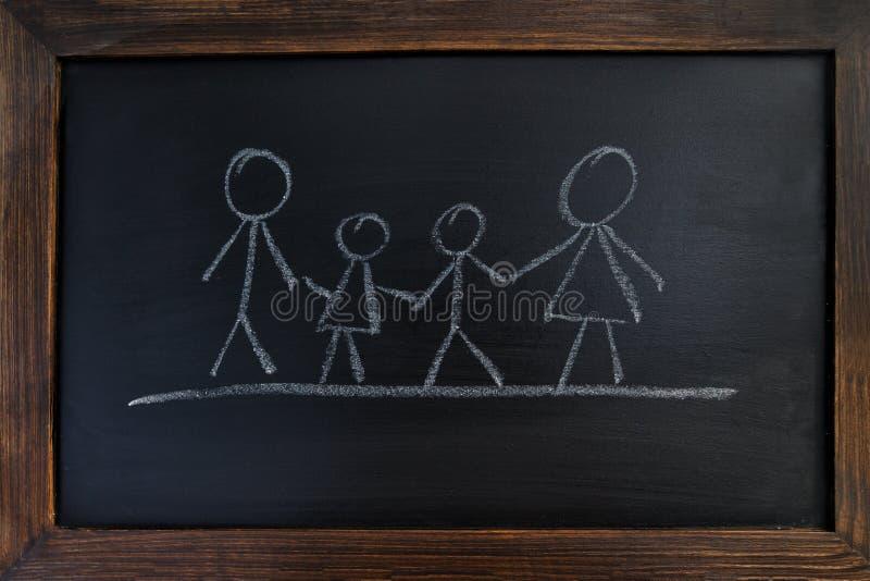 有在黑板和孩子的一个家庭画的父母 免版税库存照片
