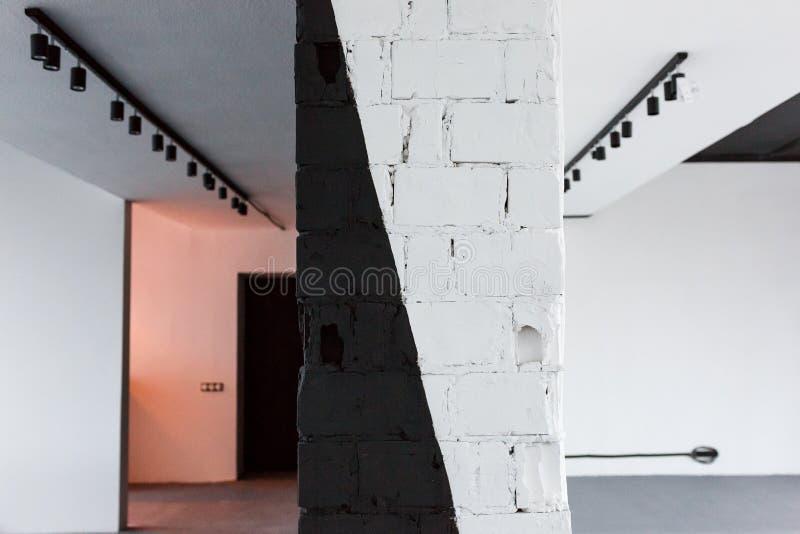 有在黑白墙壁绘的砖的空的办公室室在前面焦点 与斑点光的顶楼室内设计 库存图片