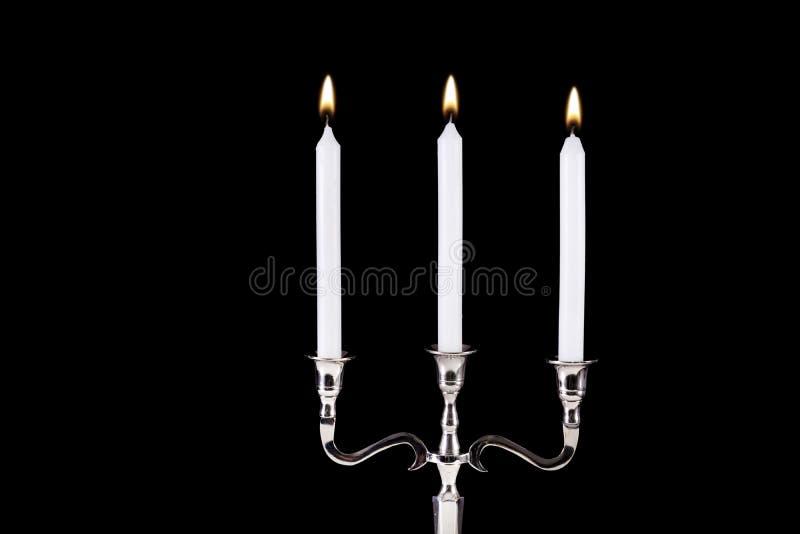 有在黑背景对光检查燃烧隔绝的白色石蜡的巴洛克式的银色烛台 免版税库存照片