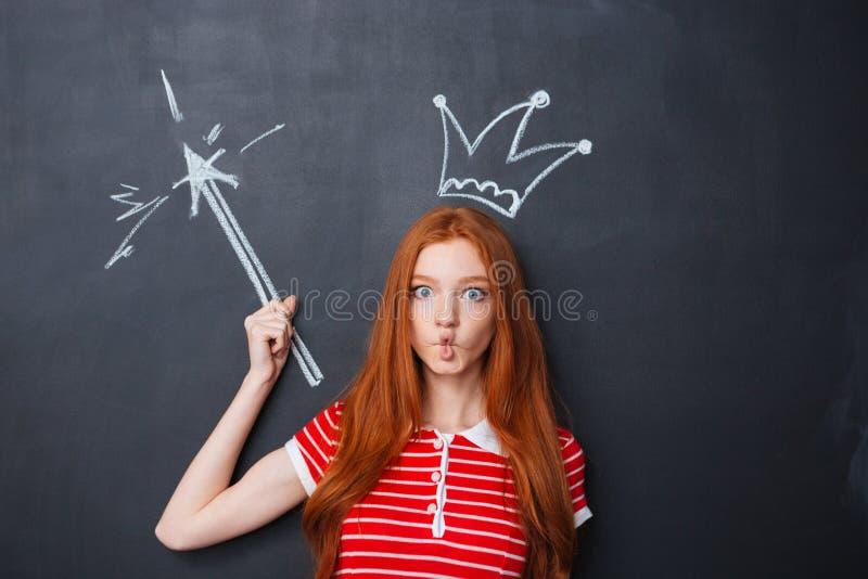 有在黑板和魔术鞭子的滑稽的妇女画的冠 库存图片