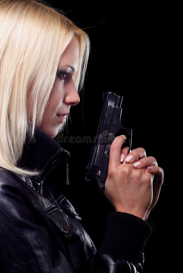 有在黑背景隔绝的枪的美丽的女孩 免版税库存图片