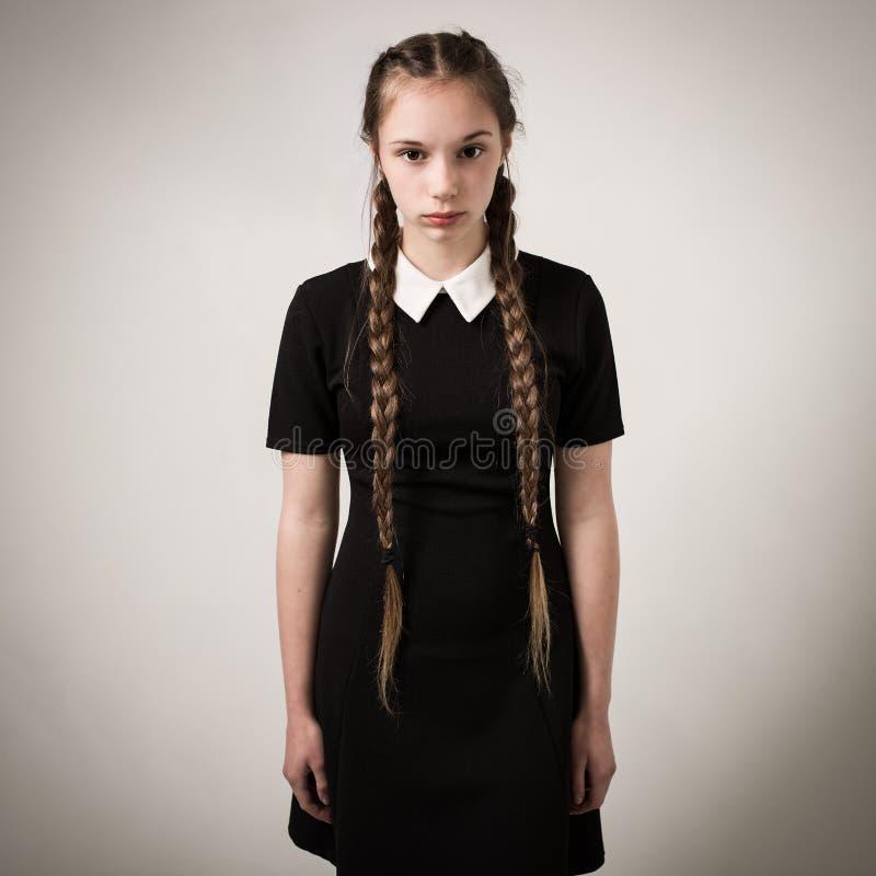 有在黑色穿戴的褶的美丽的十几岁的女孩 免版税库存照片