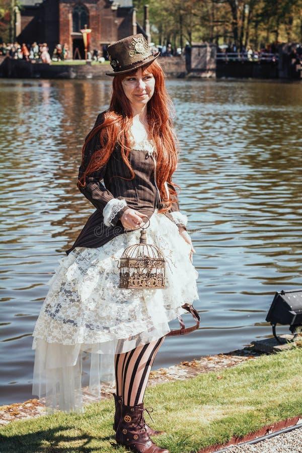 有在steampunk样式穿戴的鸟笼的美丽的夫人摆在a 库存图片