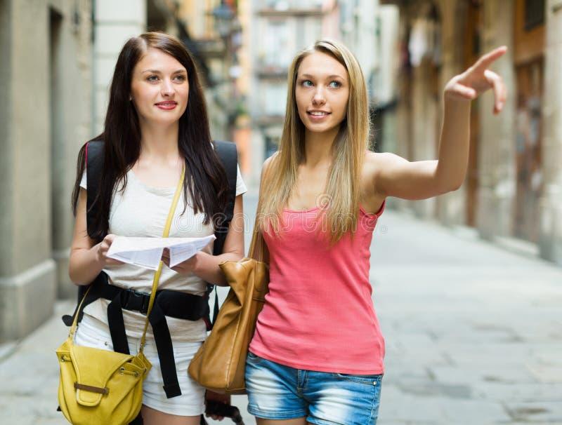有地图的两个美丽的女孩 免版税库存照片