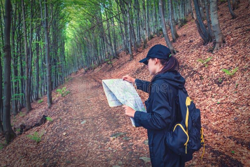 有地图的女孩在森林里 免版税图库摄影