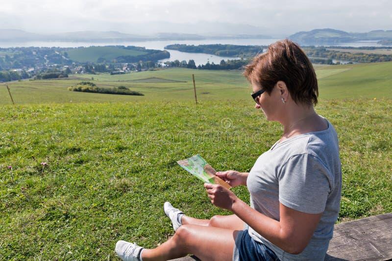 有地图的妇女在Liptovsky Trnovec,斯洛伐克附近的夏天小山 免版税图库摄影