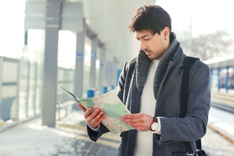 有地图的年轻人在火车站 免版税库存图片