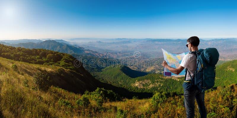 有地图背包放松的旅客室外与山 库存照片