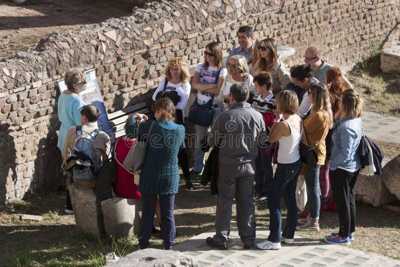 有地方指南的小组游人 废墟在罗马,意大利 免版税库存照片
