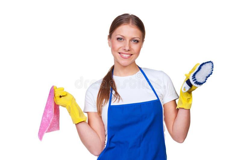 有地毯和画笔的兴高采烈的打杂的女佣人 库存图片