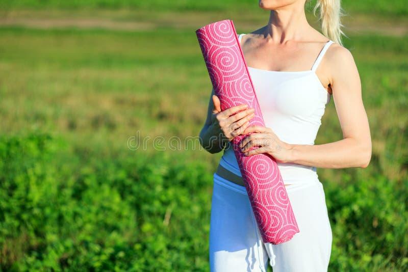 有地毯摆在的瑜伽妇女 库存照片