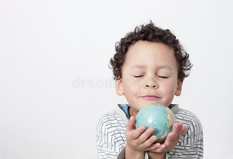 有地球的小男孩在他的手上 图库摄影