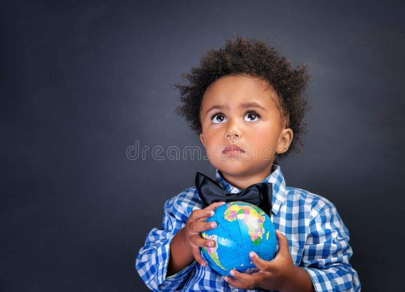 有地球的小男小学生在手上 免版税库存图片