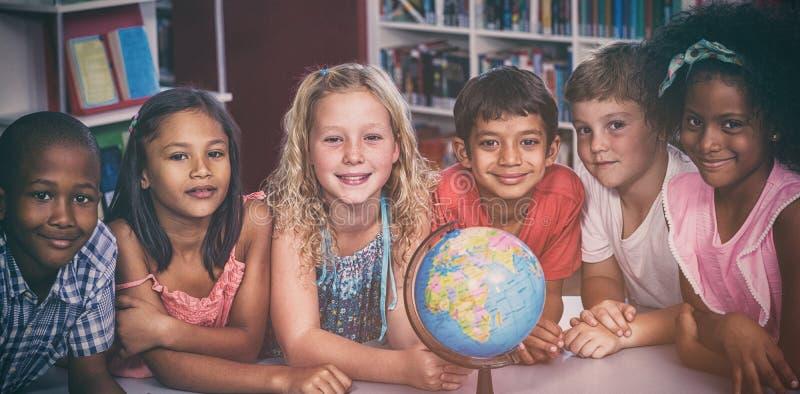 有地球的微笑的孩子在桌上 库存图片