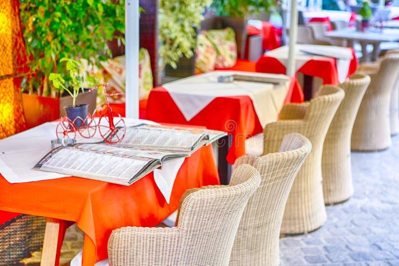 有地道秸杆椅子的经典平静的克里特岛人露天餐馆在表前面 库存图片