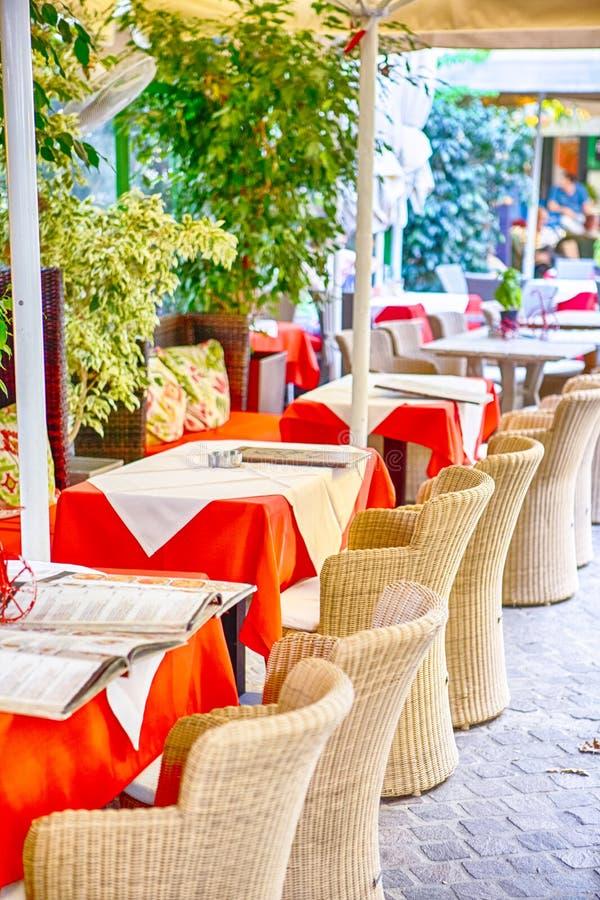 有地道秸杆椅子的经典平静的克里特岛人露天餐馆在表前面 免版税库存照片