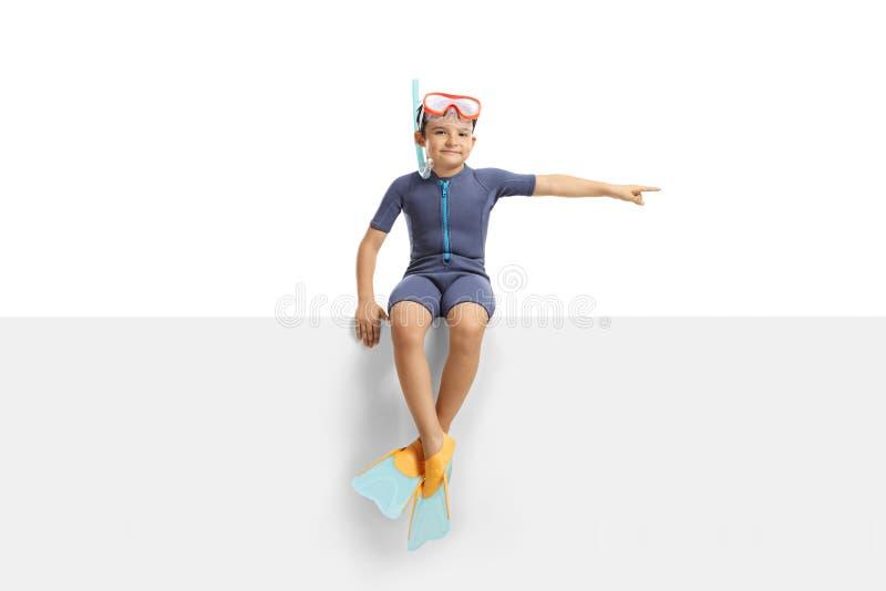 有坐一个白色盘区和指向边的一个潜水的面具和保温潜水服的男孩 图库摄影