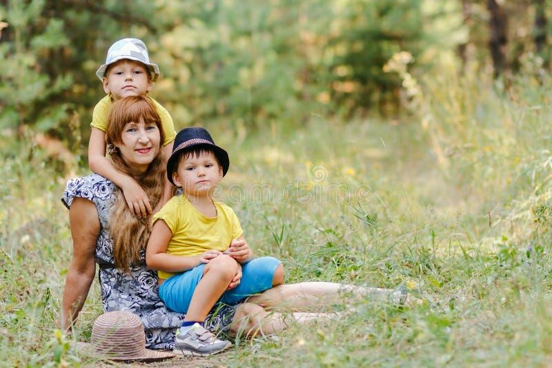 有坐两个小的孙的年轻愉快的祖母  免版税库存照片