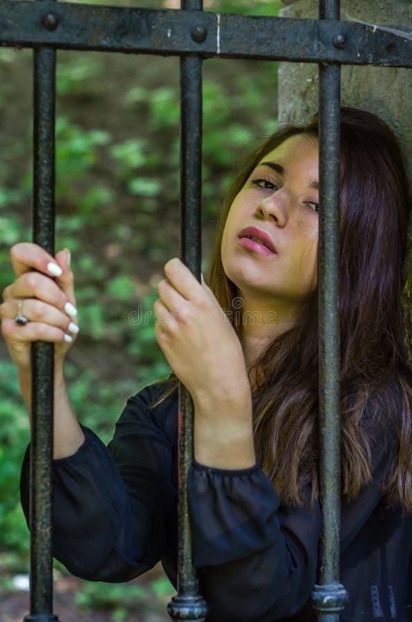 有坐关在监牢里在一所监狱的长的黑发的年轻迷人的少年女孩在服刑为的老城堡堡垒 免版税图库摄影