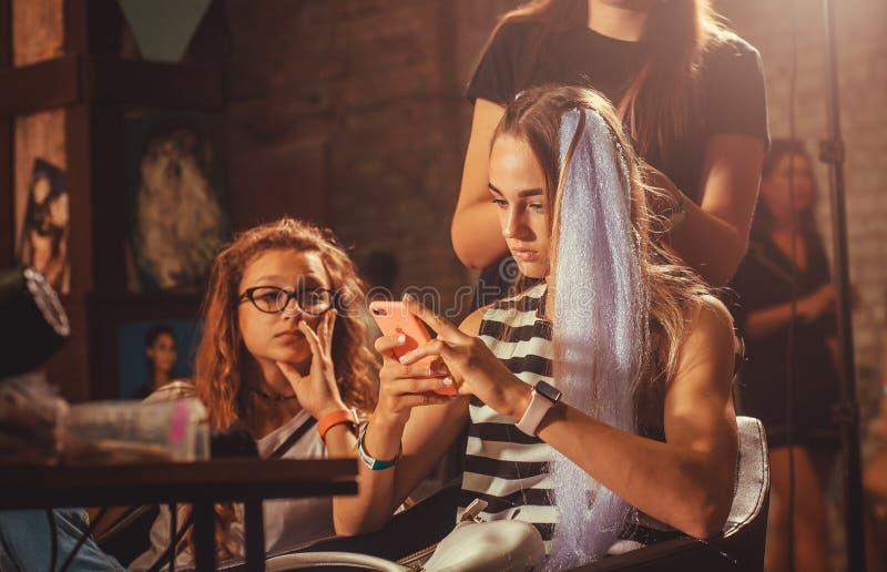 有坐和做在普遍的街道食物节日美容院的手机的女孩新的发型  免版税库存照片