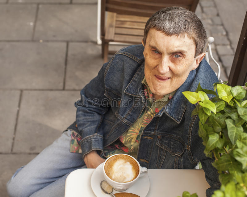 有坐咖啡馆的大脑麻痹的残疾人 免版税库存照片